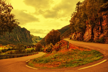 A winding country road with a steep mountain at sunset time.