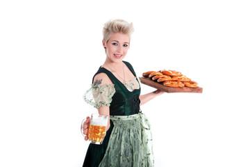 Junge Frau serviert Bier und Brezen auf Oktoberfest imDirdl
