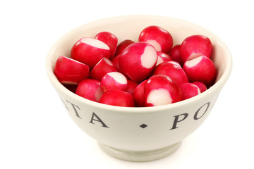 prepared red radishes in a white ceramic bowl on a white backgro