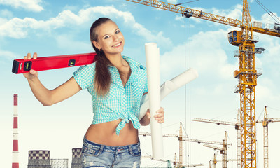 Woman holding builders level on shoulder and paper scrolls in