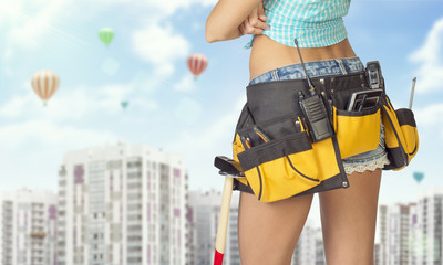 Woman in tool belt standing backwards. Cropped image. High-rise