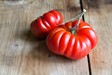 Red tomato on wooden background