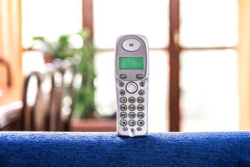 cordless phone on a blue sofà