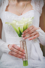 Wedding bouquet of flowers in hands of beautiful young bride