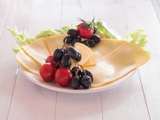 Käsescheiben mit Tomaten und Weintrauben