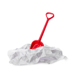 Red plastic toy shovel in paper