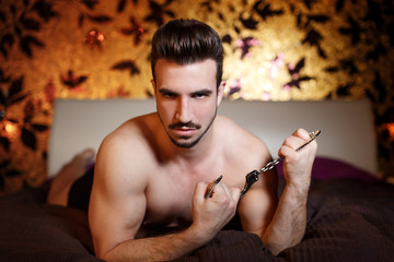 Sexy macho man laying with handcuffs