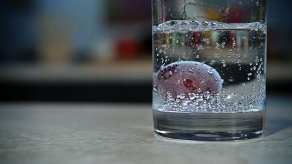 Still life. Grape floating in a glass of sparkling water