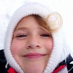 Niña con gorro blanco en la nieve