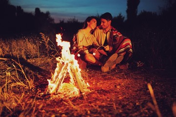 a charming couple sitting around the campfire