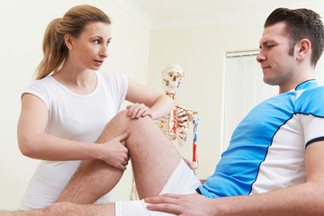 Osteopath Treating Male Patient With Sports Injury