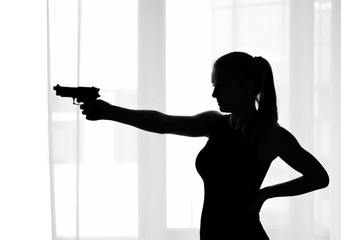 Silhouette of the girl with a gun