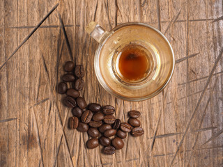 Empty cup of espresso coffee with coffee crop beans on wood back