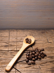 Coffee crop beans on bamboo spoon and wooden texture background