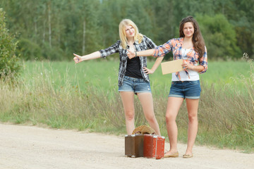 Students girls hitchhiking with cardboard