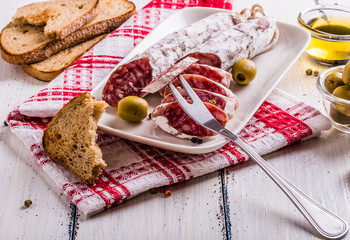 Slices of salami on a white plate