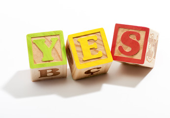 Yes in Wooden Letter Blocks on White Background