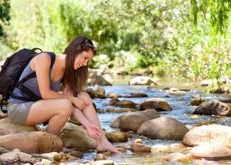 Young woman sitting by stream with backpack