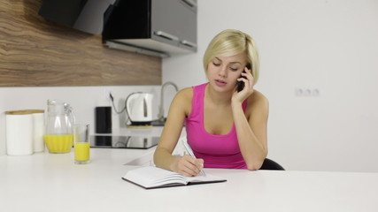 Woman speaking mobile phone call kitchen, make note writing