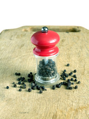 Black peppercorn and manual mill with red cap on kitchen board