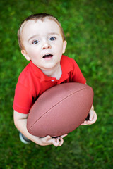 Happy Young Boy Posing with Football Outside