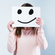 woman holding a cardboard with a smiley face