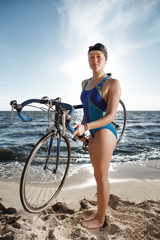 Young woman in swimsuit posing with road bike