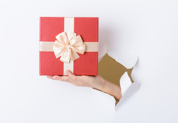 Woman hand hold with present box break through the paper wall
