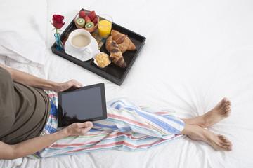 woman bed tablet breakfast