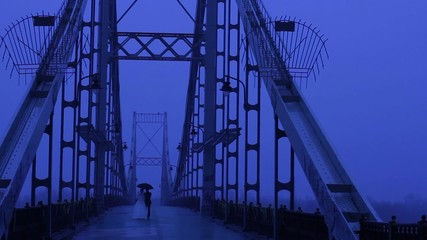Lone pair walking through the night bridge