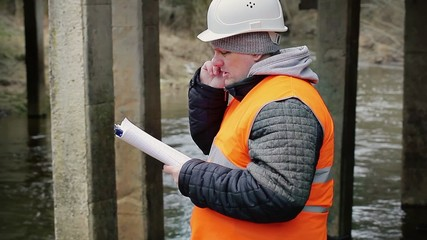 Engineer talking on the cell phone under the bridge