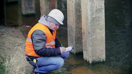 Engineer writing documentation near the bridge supports