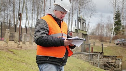 Engineer reading documentation at power plant sluice