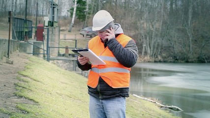 Engineer with cell phone and documentation at power plant sluice
