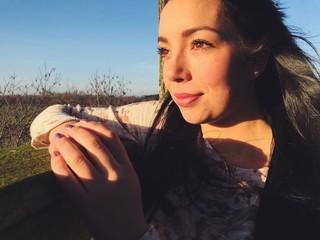 Junge Frau blickt in die Sonne
