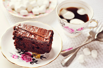 Chocolate cake on a plate and a cup of coffee