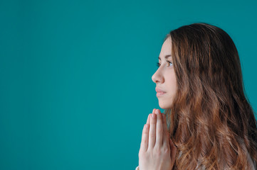young woman praying with her hands folded