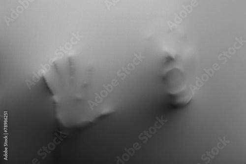 Leinwanddruck Bild Screaming human face with hand pressing through fabric as