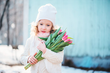 early spring portrait of child girl with pink tulips on the walk