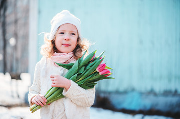 child girl with bouquet of tulips in early spring