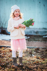 happy child girl with bouquet of tulips walking in early spring