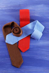 Colorful male ties on color wooden table background