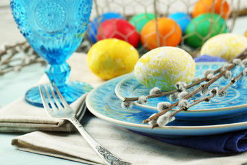 Easter table setting on color wooden background