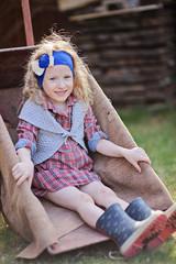 happy child girl sitting in wheelbarrow in spring garden
