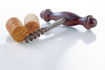 Traditional corkscrew with corks on glass table