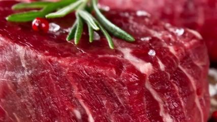 Pan zoom of raw beef steaks on wood