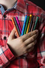 Niño con rotuladores de colores en la mano.