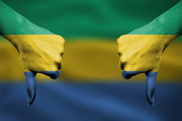 failure of Gabon - hands gesturing thumbs down in front of flag