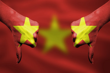 failure of Vietnam - hands gesturing thumbs down in front of fla