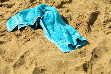 closeup of blue towel on a sandy beach. Relax.